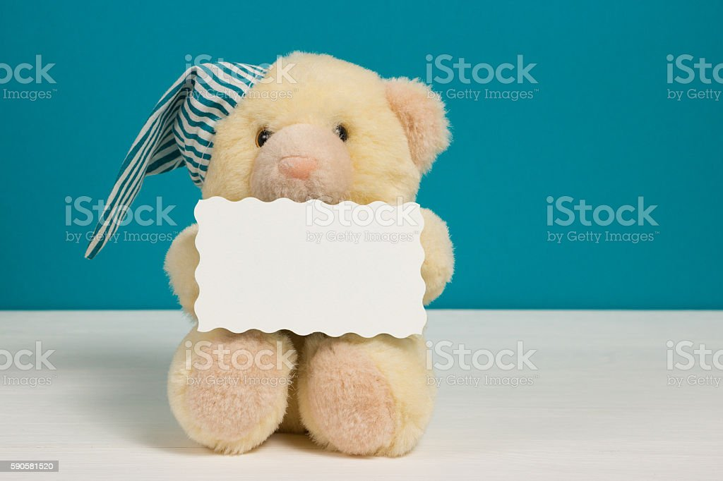 Cute beige bear with nightcap and card on white-blue background stock photo