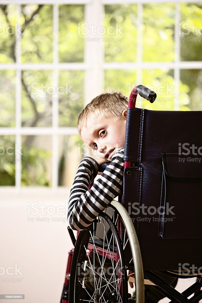 Cute blond boy in wheelchair smiles wistfully over his shoulder stock photo