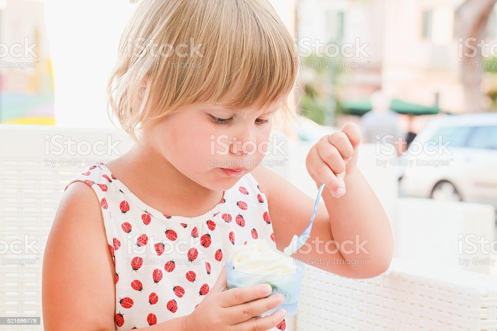 Cute blond Caucasian baby girl eats ice cream stock photo