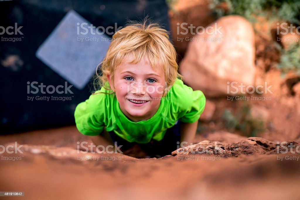 Cute Blond Caucasian Boy Smiling and Climbing a Rock stock photo