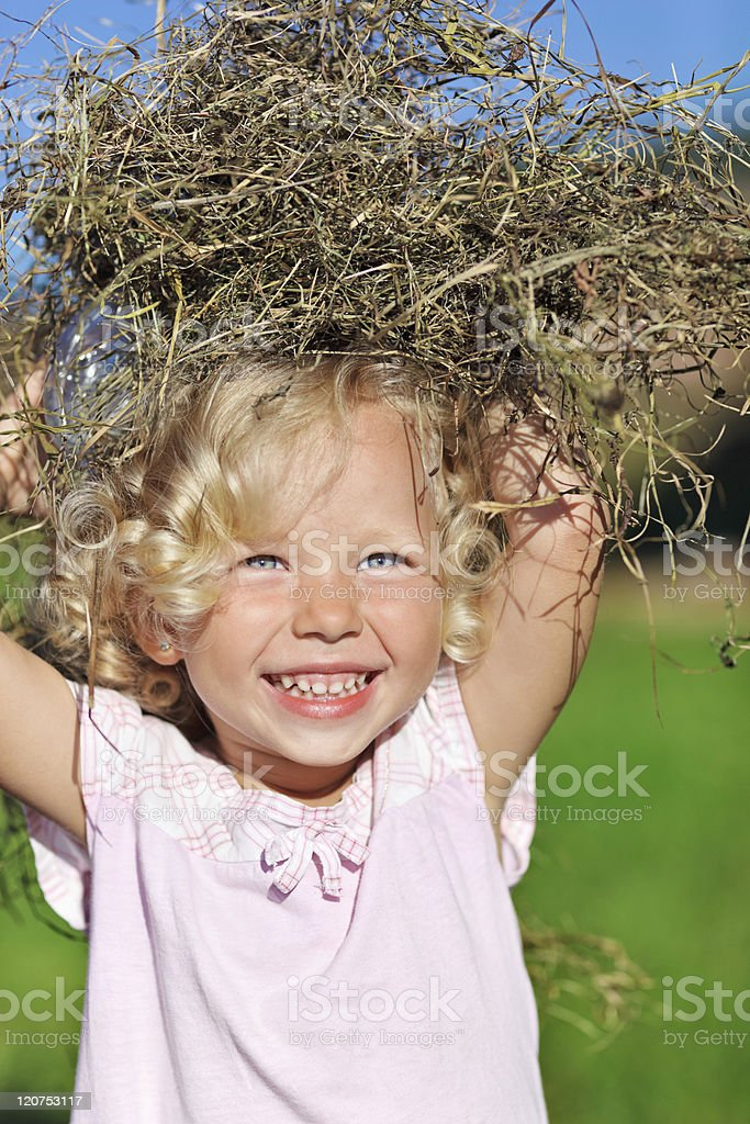 Cute blond curly-haired little girl playing with hay royalty-free stock photo