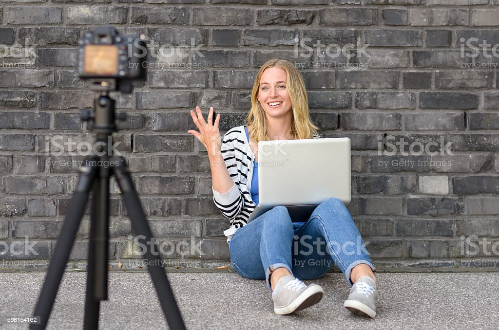 Cute blond female blogger with laptop recording video stock photo