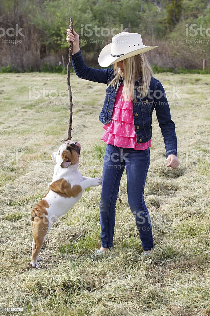Cute Blond Girl Playing with Her English Bulldog Puppy Outdoors royalty-free stock photo
