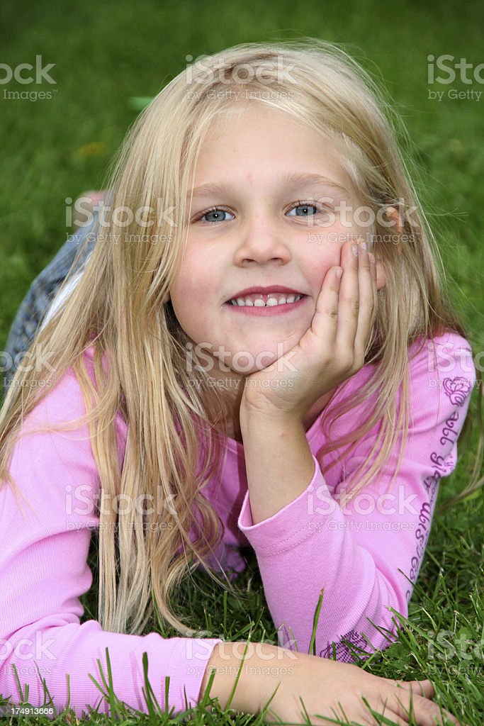 cute blond girl relaxing in the grass stock photo