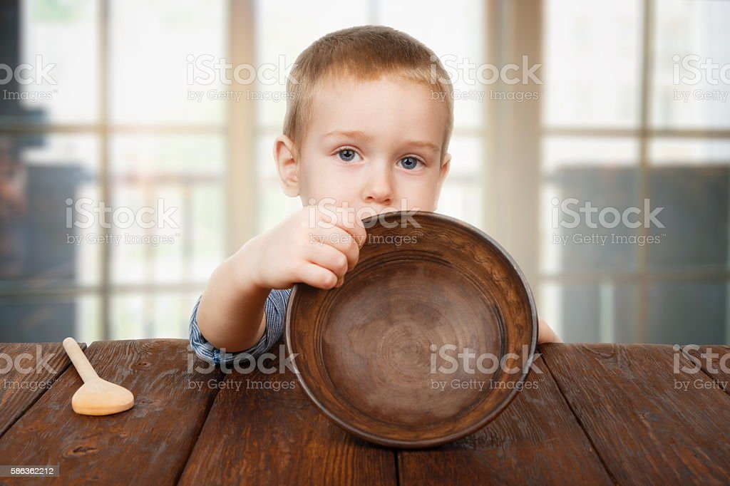 Cute blonde boy shows empty plate, hunger concept stock photo