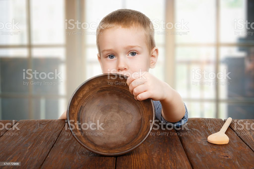 Cute blonde boy shows empty plate stock photo