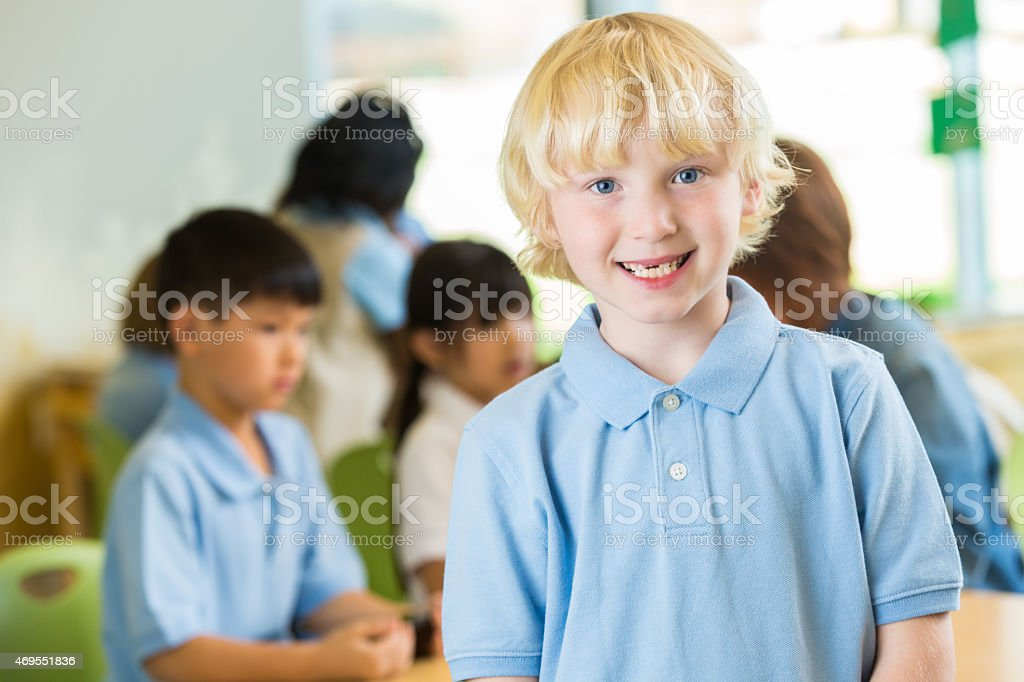 Cute blonde elementary age boy in private school classroom stock photo