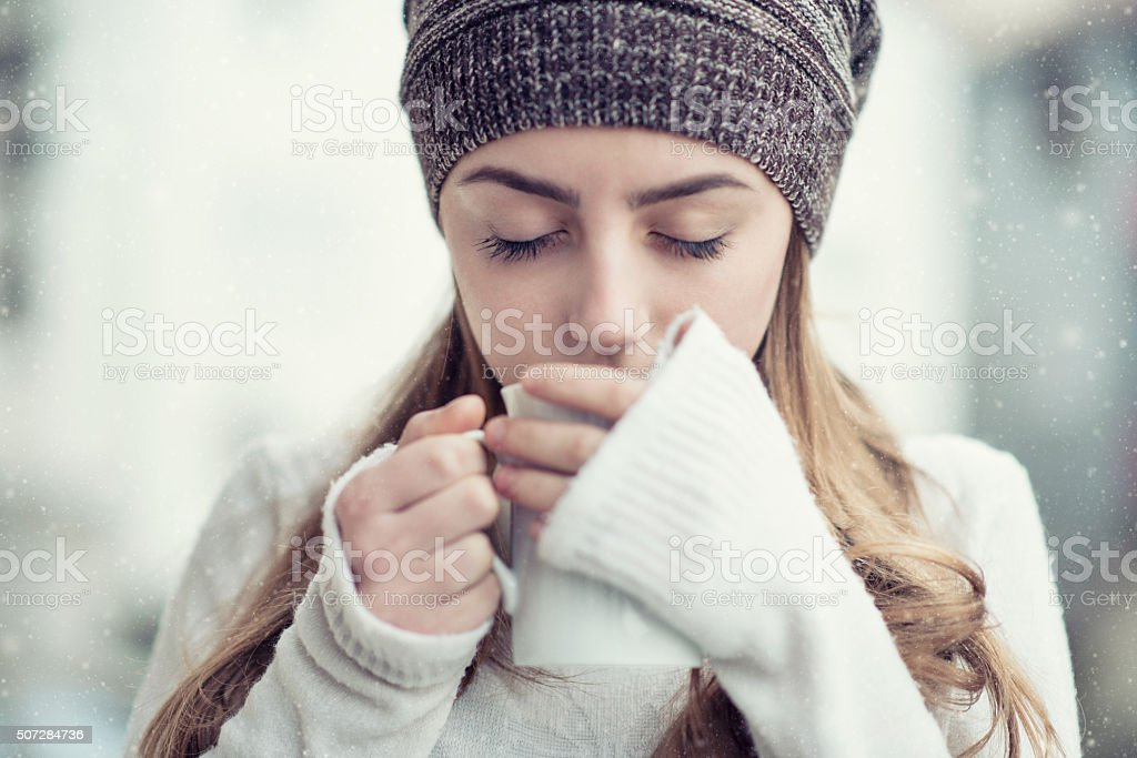 Cute Blonde Girl Drinking hot Tea During the Winter Snow stock photo
