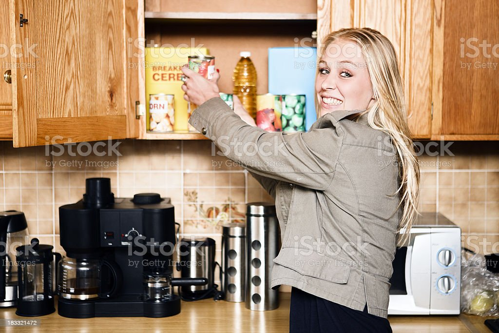 Cute blonde in kitchen, reaching into grocery cupboard royalty-free stock photo