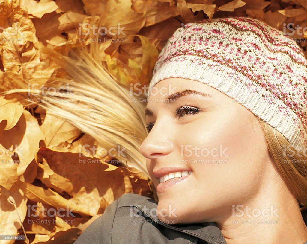 Cute blonde laying down on tree leaves royalty-free stock photo