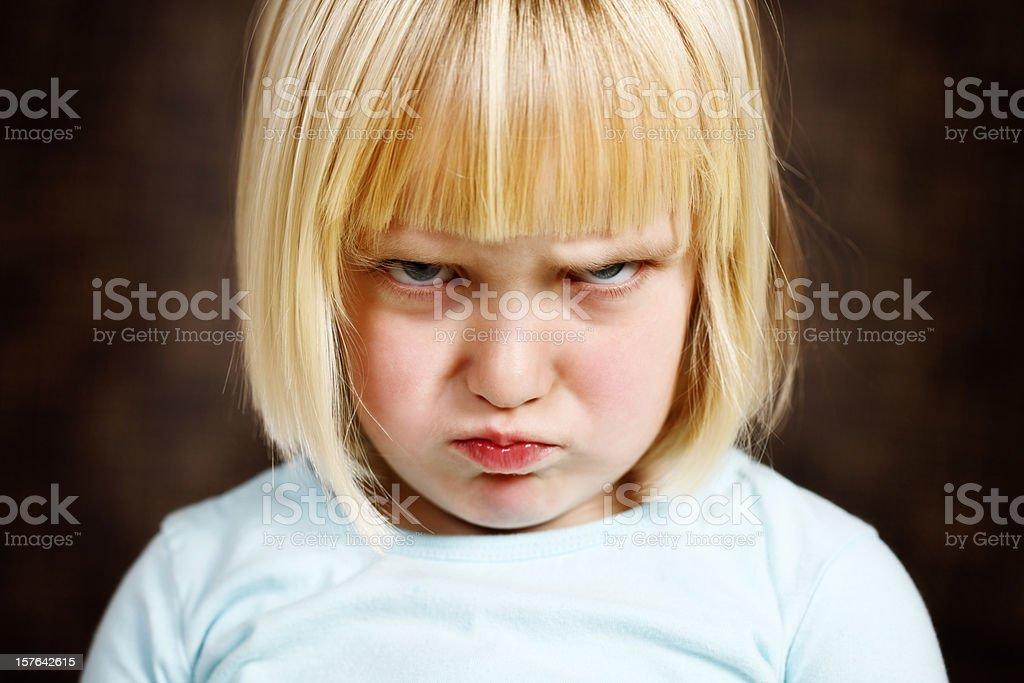Cute blonde toddler girl scowls at camera royalty-free stock photo