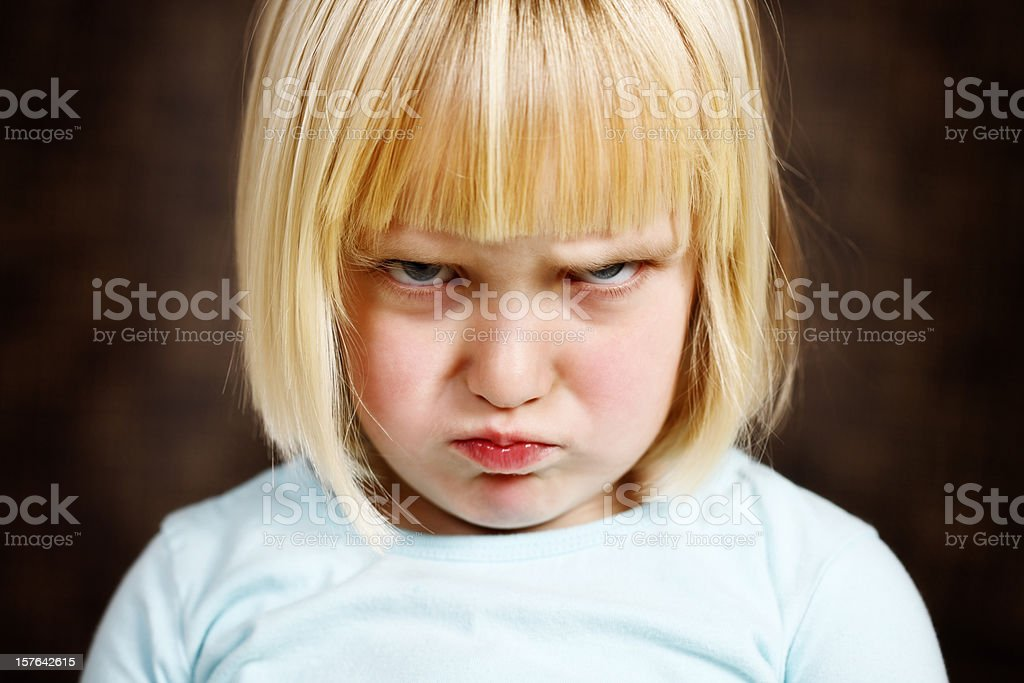 Cute blonde toddler girl scowls at camera stock photo
