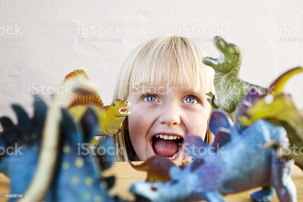 Cute blonde toddler roars at her ferocious toy dinosaurs stock photo