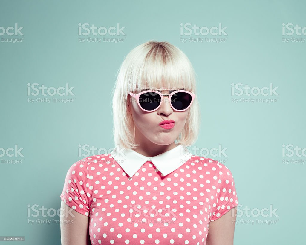 Cute blonde young woman wearing polka dotted dress making faces stock photo