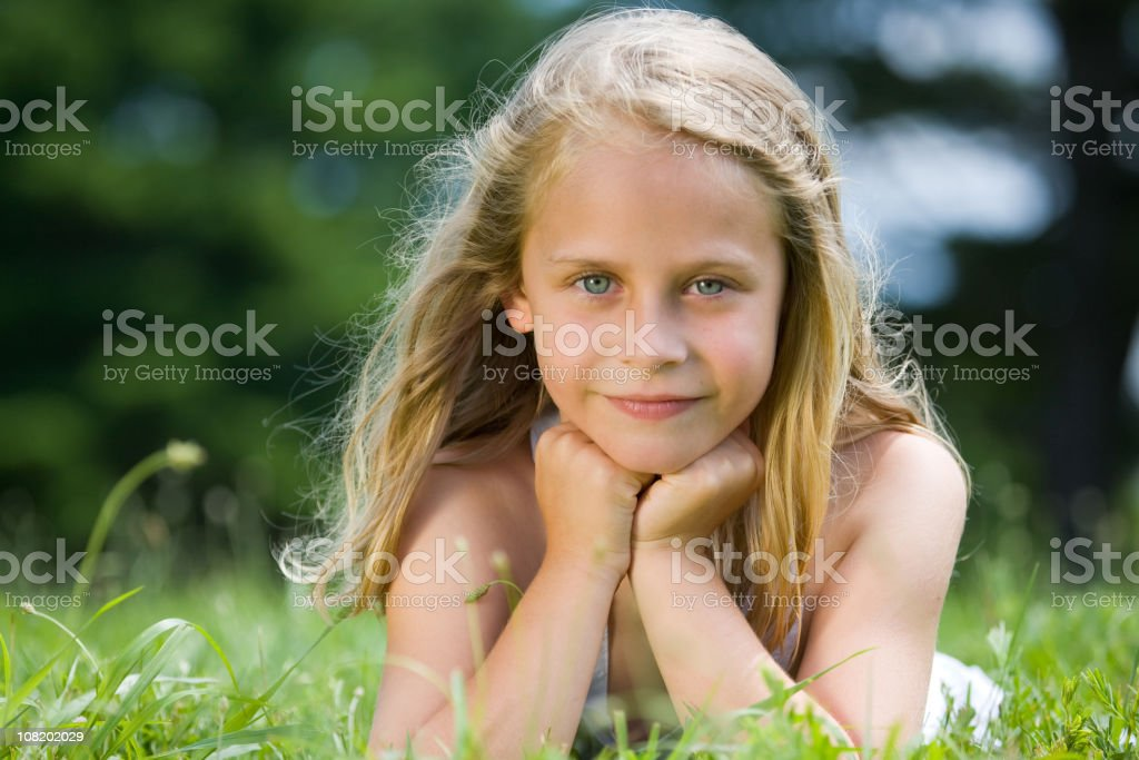 Cute blue-eyed little girl gazes at the camera royalty-free stock photo