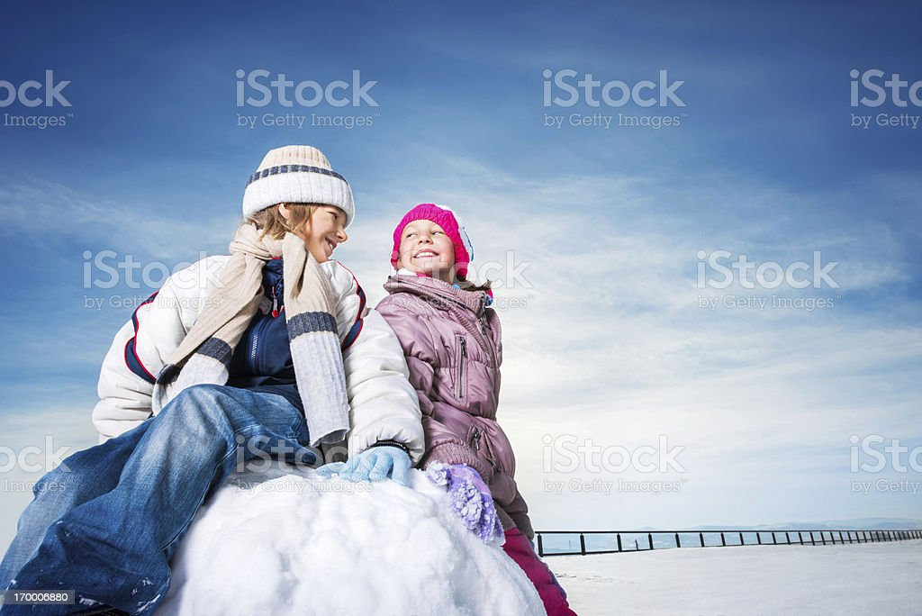 Cute boy and girl enjoying in the snow. royalty-free stock photo
