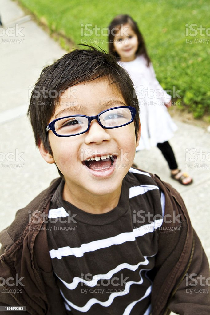 cute boy at the park with sister behind royalty-free stock photo