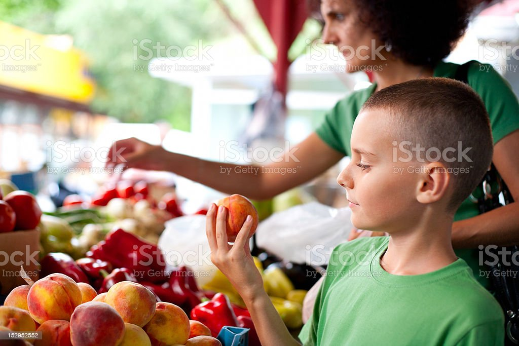 Cute boy buying vegetables stock photo