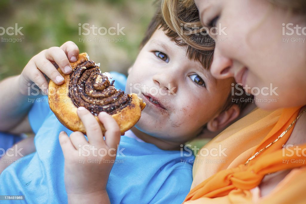 Cute boy eating chocolate snail royalty-free stock photo
