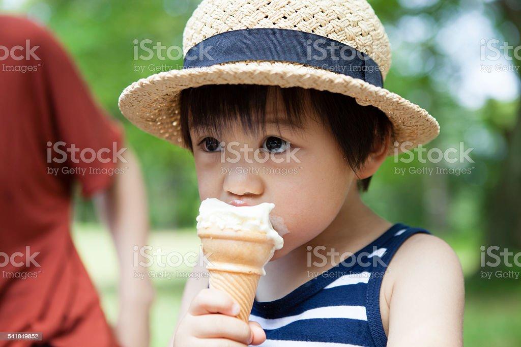 Cute boy eating ice cream stock photo