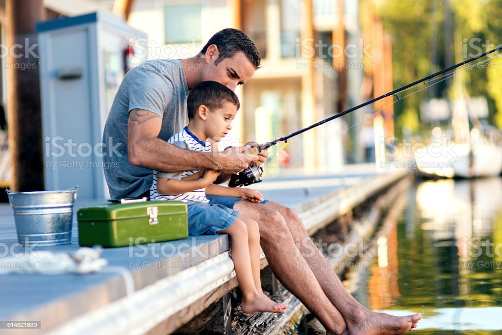 Cute boy gets taught how to fish from dad stock photo