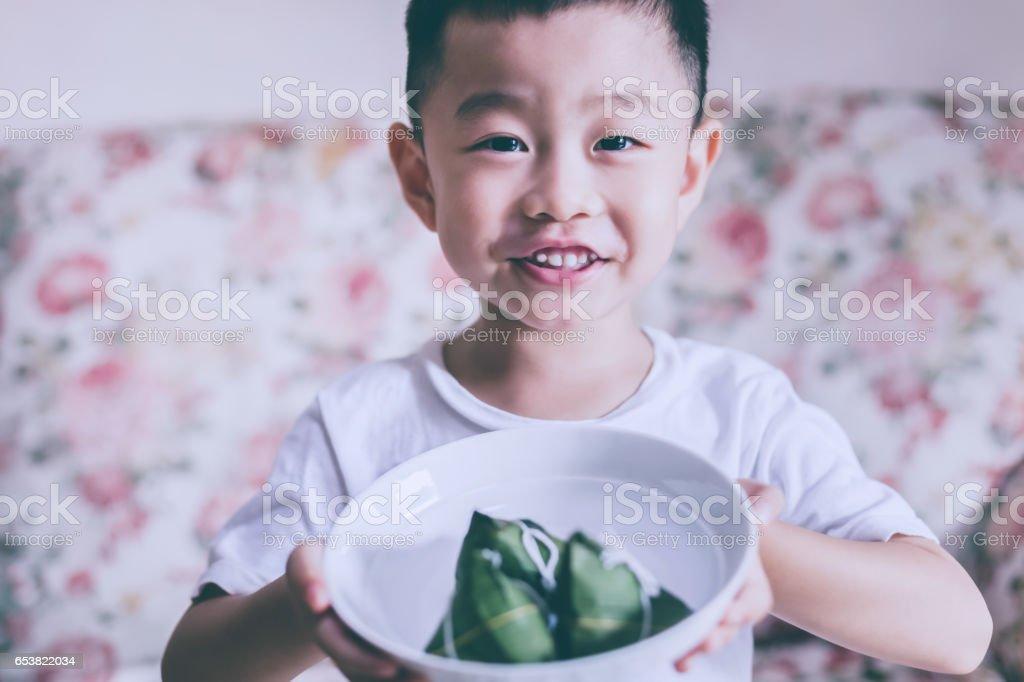 Cute boy holding zongzi stock photo