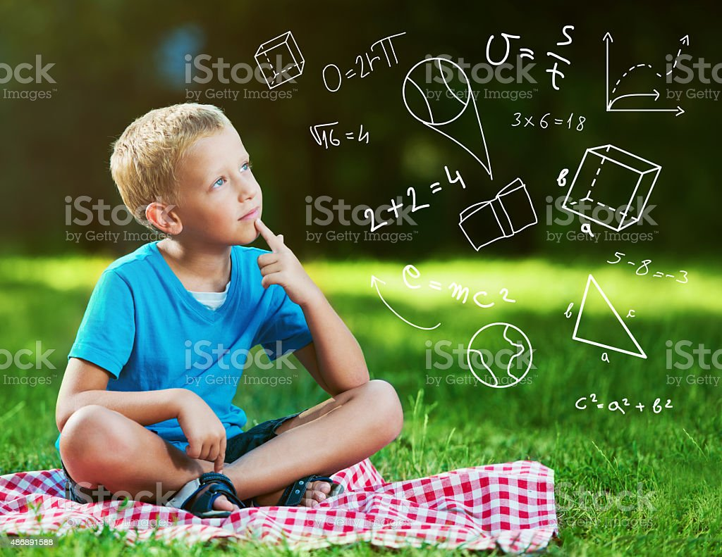 Cute boy in a park thinking stock photo