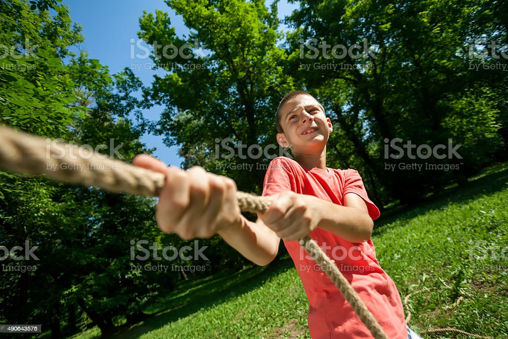 Cute boy in red pulling rope stock photo