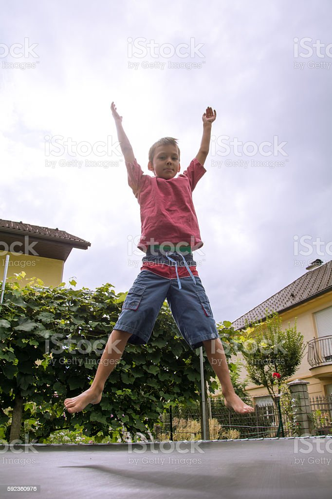Cute boy jumping on trampoline stock photo