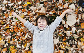 Cute boy laying on the autumn leaves