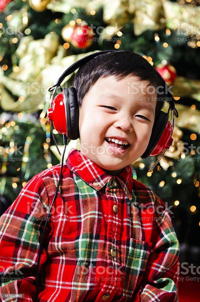 Cute boy listening to Christmas music royalty-free stock photo