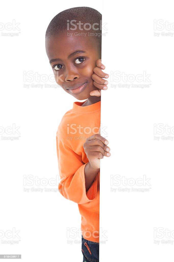 Cute boy looking around corner stock photo
