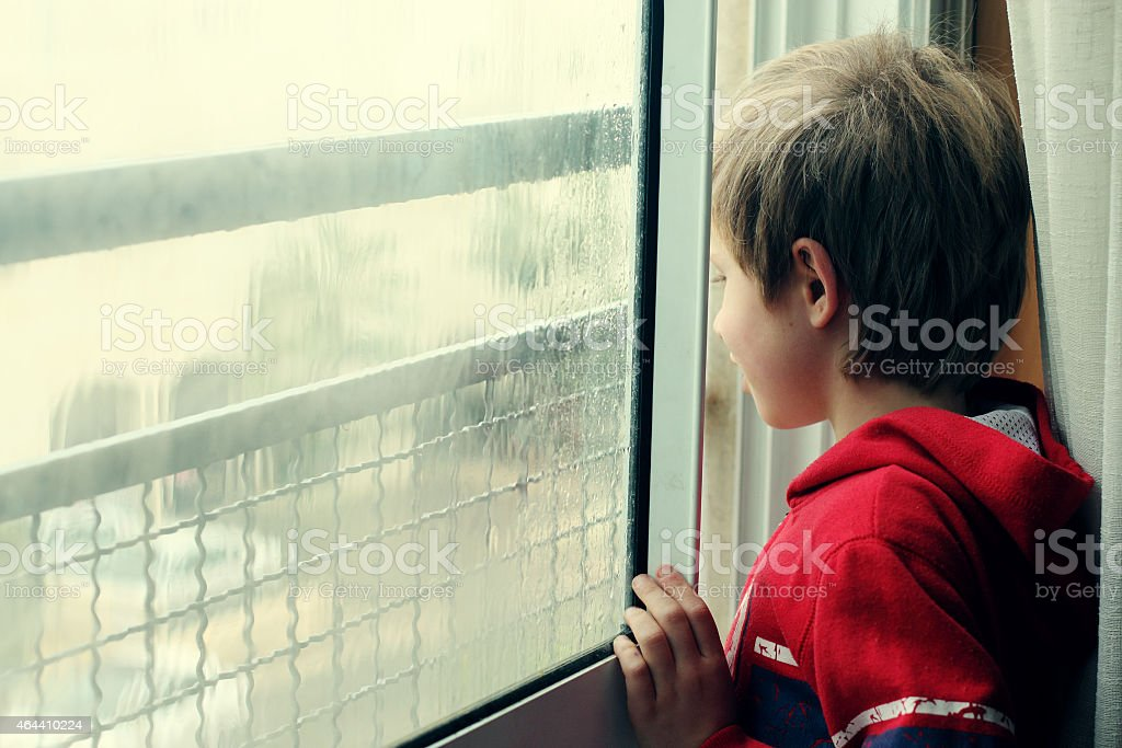 Cute boy looking through the window stock photo