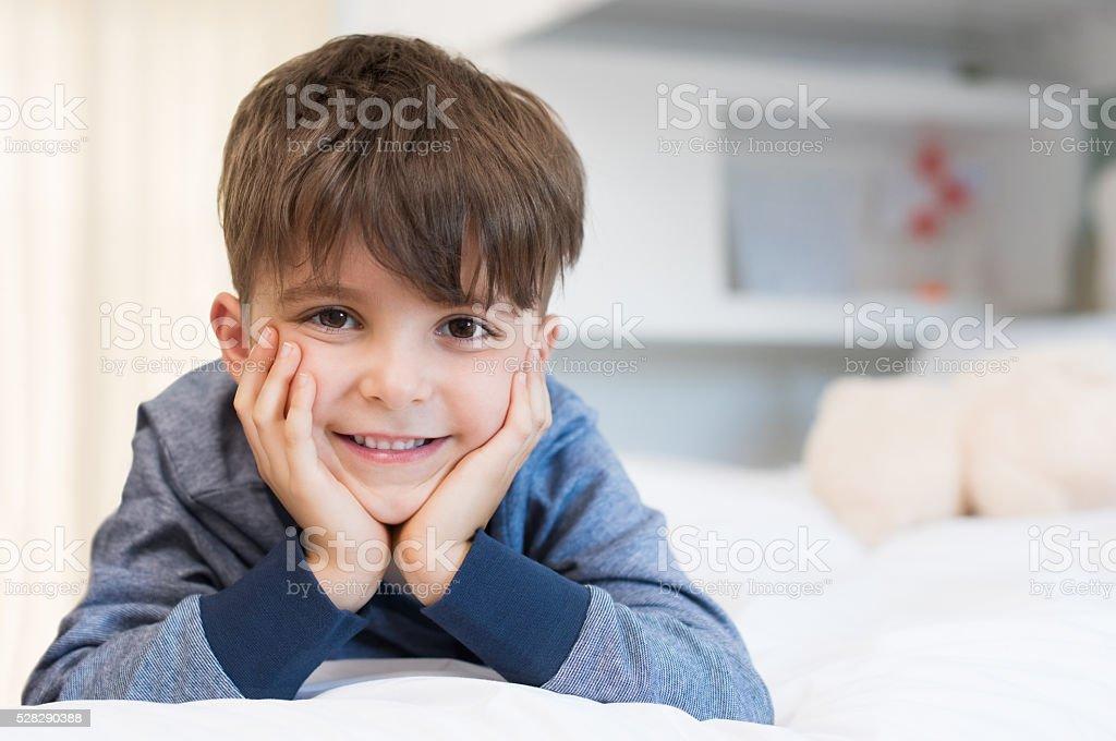 Cute boy lying on bed stock photo