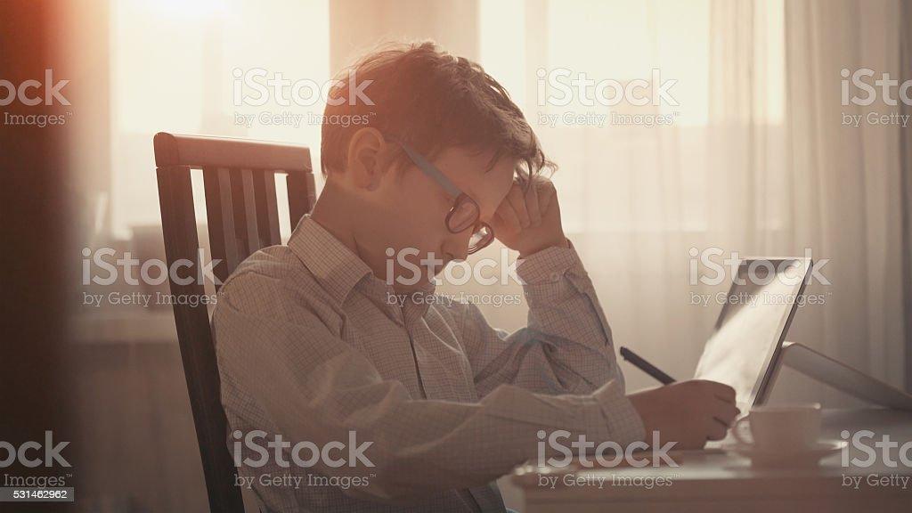 Cute boy making his homework stock photo