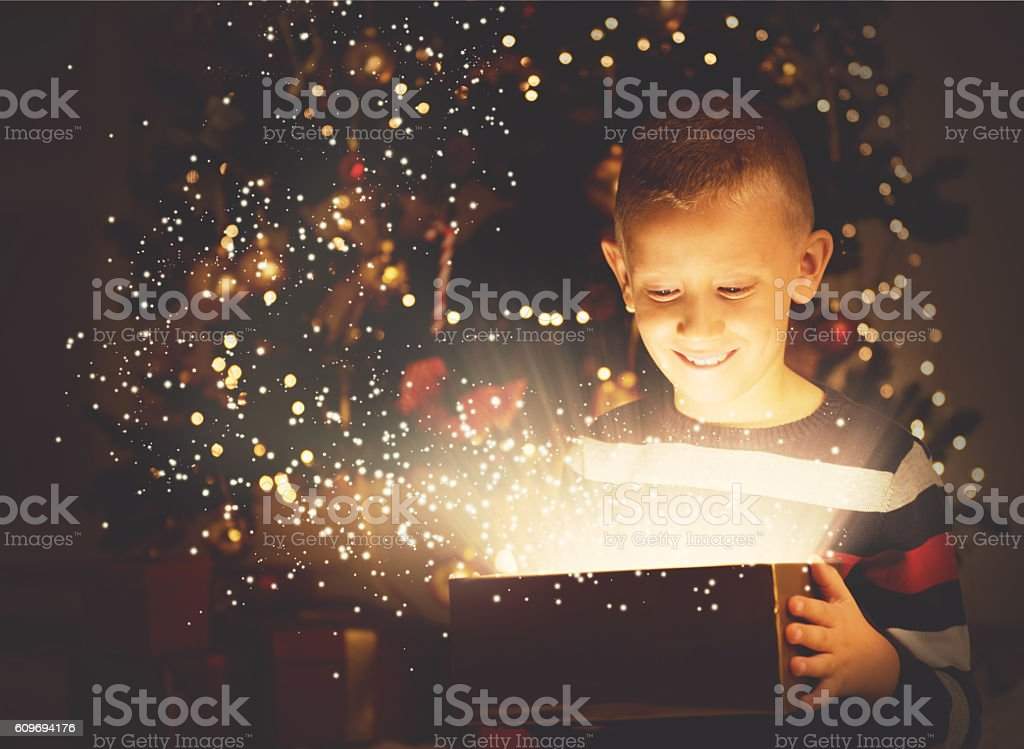 Cute boy opening a magical present on Christmas eve stock photo