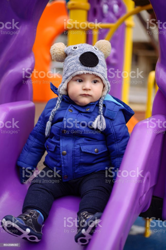 Cute boy playing on a playground slide stock photo