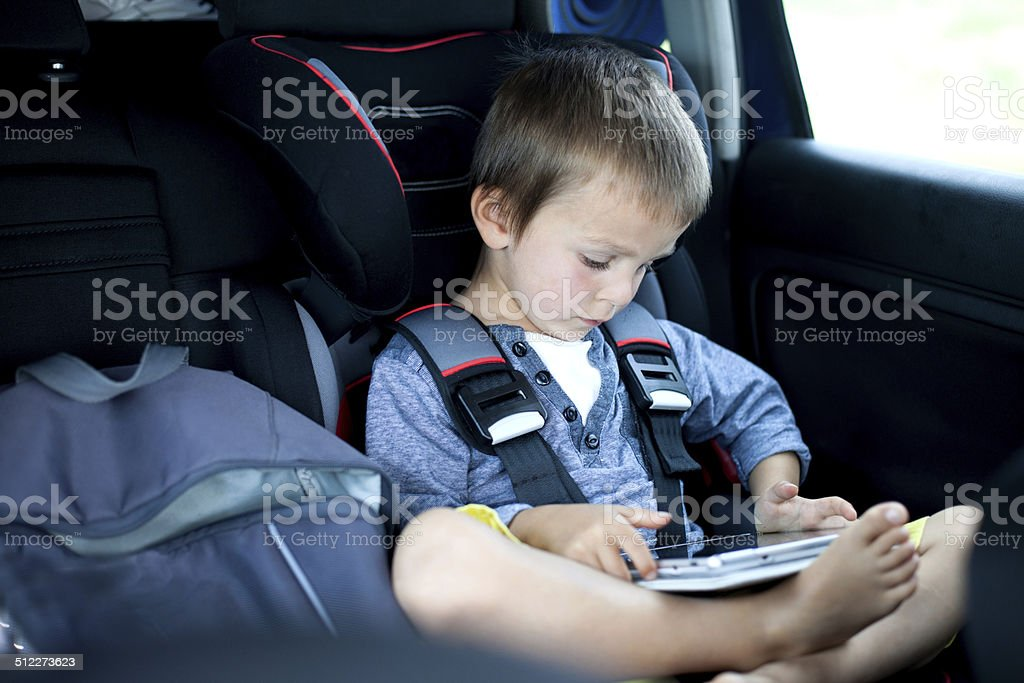 Cute boy, playing on tablet in the car stock photo