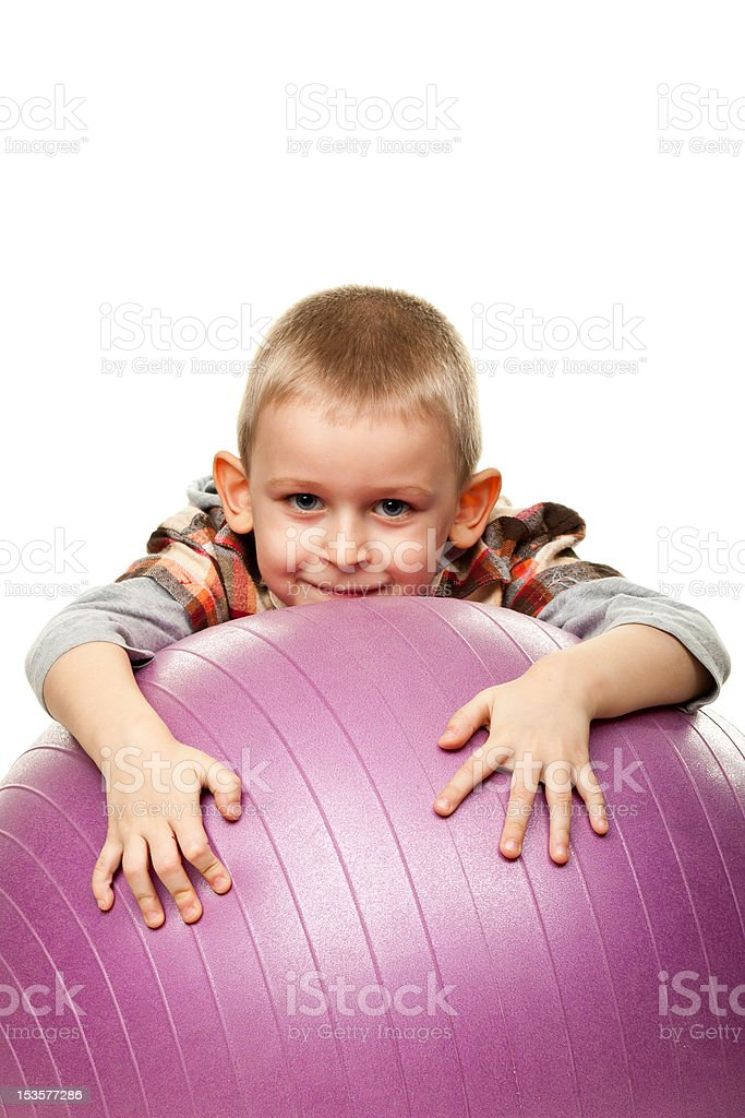 Cute boy playing with fit ball stock photo