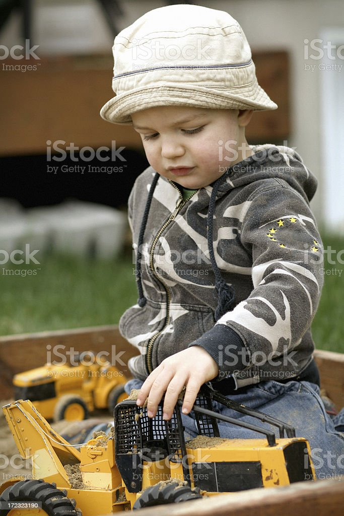 Cute boy playing with his toys stock photo