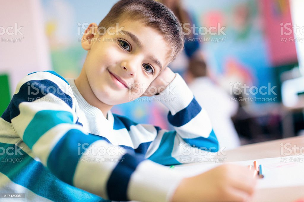 Cute boy possing for the camera in the class room stock photo