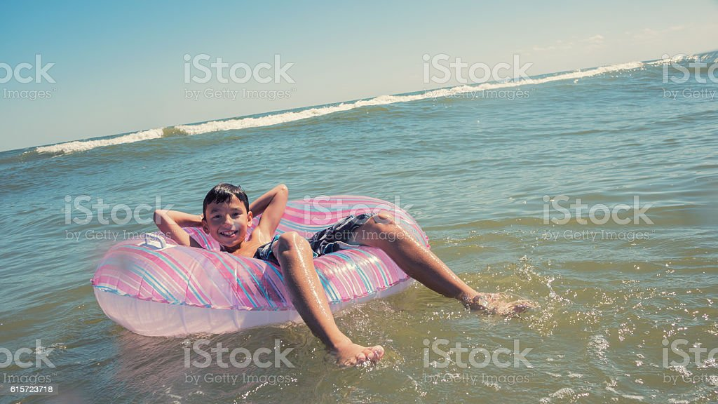 Cute boy relaxing at the beach in inner tube stock photo