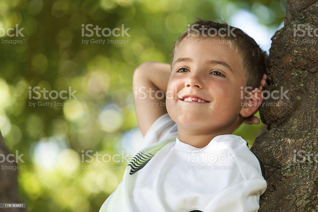 Mignon petit garçon se détendre sur Tronc d'arbre. photo libre de droits