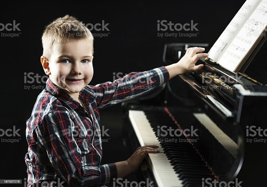 Cute boy sitting at the piano. royalty-free stock photo
