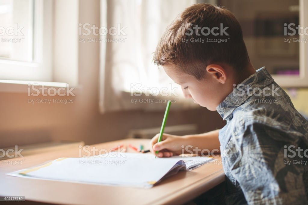 Cute boy sitting at the table doing his homework. stock photo