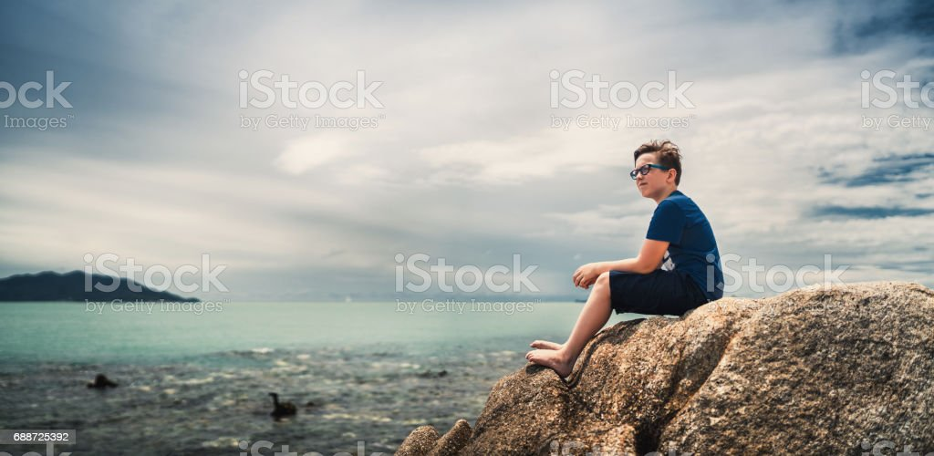 Cute boy sitting on rocks and watching at tranquil sea stock photo