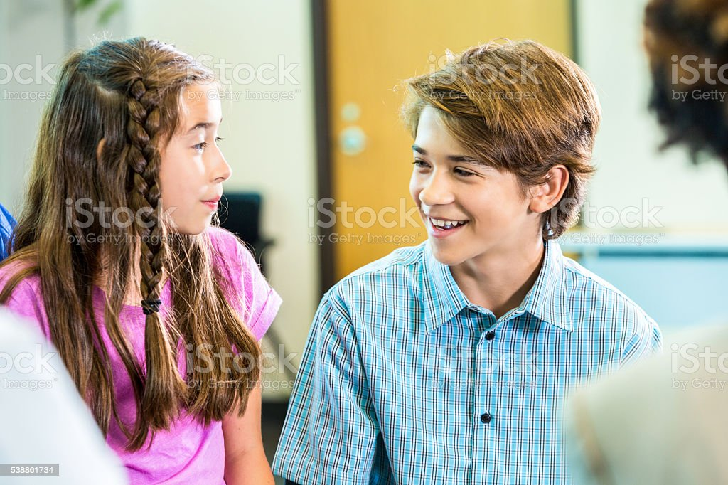 Cute boy smiling at a girl stock photo