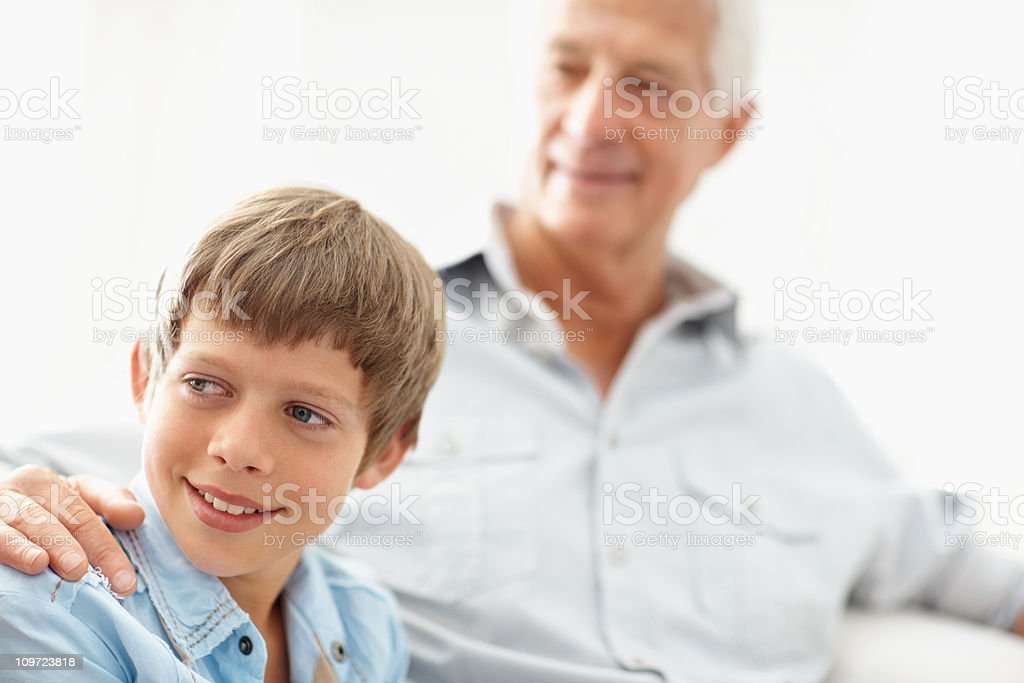 Cute boy smiling with grandfather in the background royalty-free stock photo