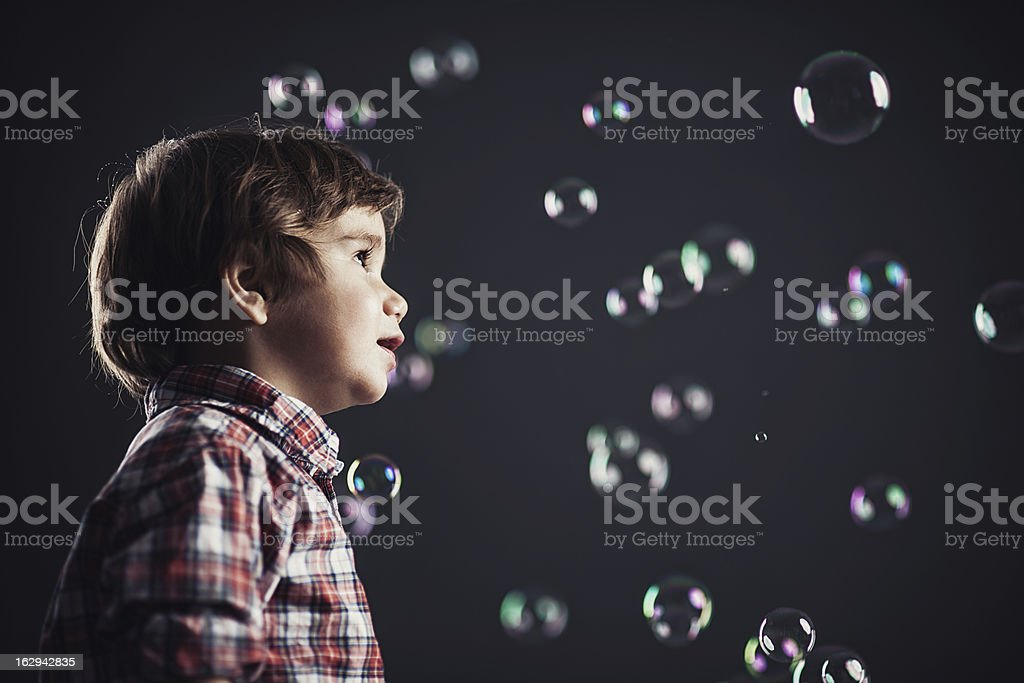 Cute boy surounded by bubbles royalty-free stock photo