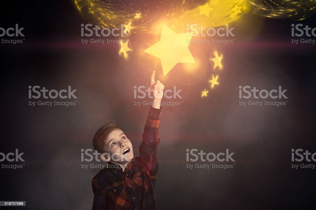 Cute Boy Touching a Glowing Yellow Star Over Him stock photo